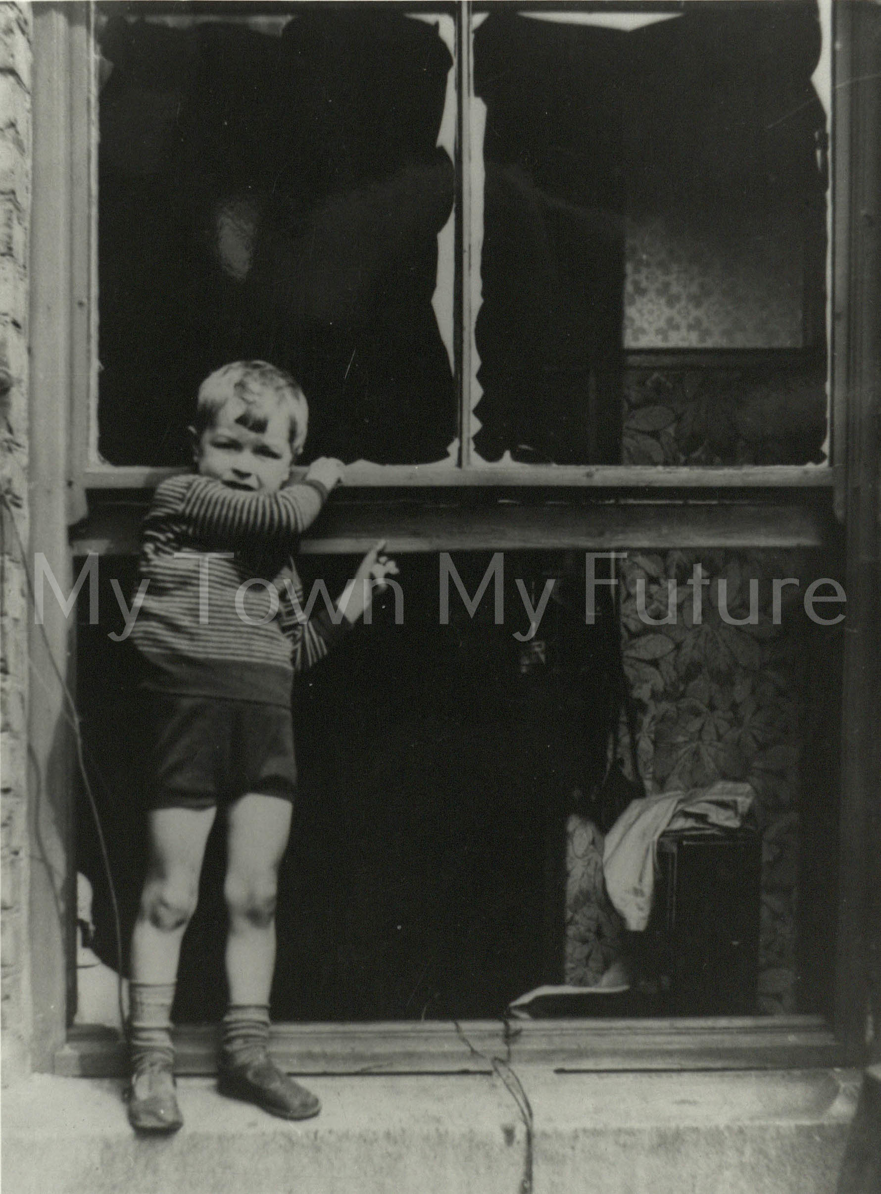 South Bank 4yr old Richard Walkington who thanfully escaped injury 1940 1942 Standing in the window of his bombed house